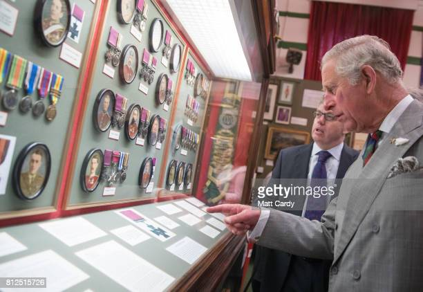 Prince Charles Prince of Wales looks at historic medals as he visits the Royal Welsh Regimental Museum during The Prince of Wales' annual Summer...
