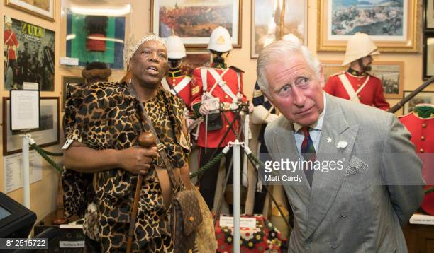 Prince Charles Prince of Wales meets Elliot Ngubane dressed in traditional Zulu costume at the Royal Welsh Regimental Museum during The Prince of...