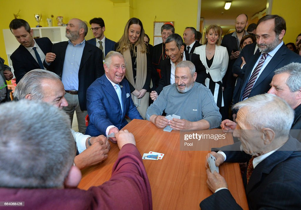 Prince Charles, Prince of Wales plays cards with a group of residents at the Caritas refugee centre during day 4 of their visit to Italy, on April 3, 2017 in Florence, Italy.