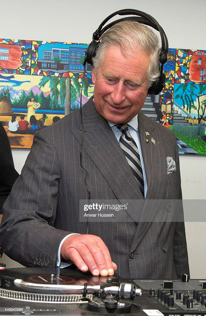 Prince Charles, Prince of Wales puts on headphones as he learns how to scratch and fade with a turntable as he visits an employment skills workshop at Yonge Street Mission and UforChange on day 2 of an official Diamond Jubilee Tour of Canada on May 22, 2012 in Toronto, Canada.