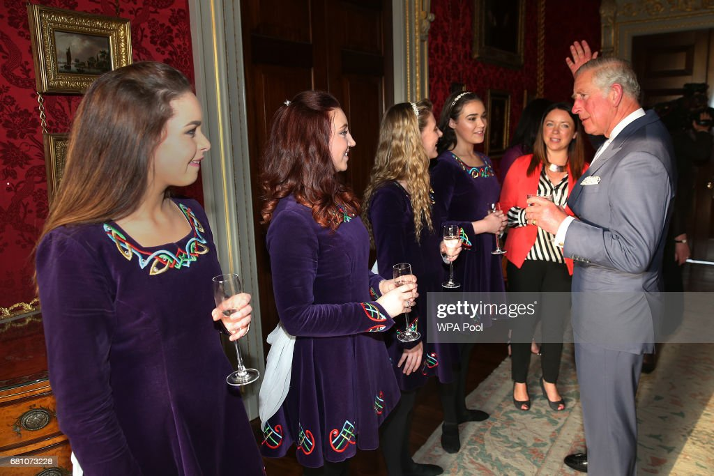 Prince Charles, Prince of Wales raises his hand as he discusses Irish dancing techniques with the Tir na N-Og Irish Dancers left-right) Sarah White, Rose McAuley, Zoe McGarry, Naomi Brown and their teacher Bronagh Craig at a Music & Words for a Spring Evening at Hillsborough Castle during a visit to Northern Ireland on May 9, 2017 in Hillsborough, County Down, Northern Ireland.