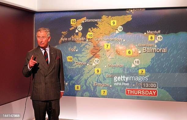 Prince Charles Prince of Wales reads the weather in the Six O'Clock studio during a tour of the BBC Scotland Headquarters where they met staff to...
