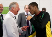 Prince Charles Prince of Wales shares a joke with a member of the Jamaican Commonwealth Boxing Team as he visits the Emirates Arena and Chris Hoy...