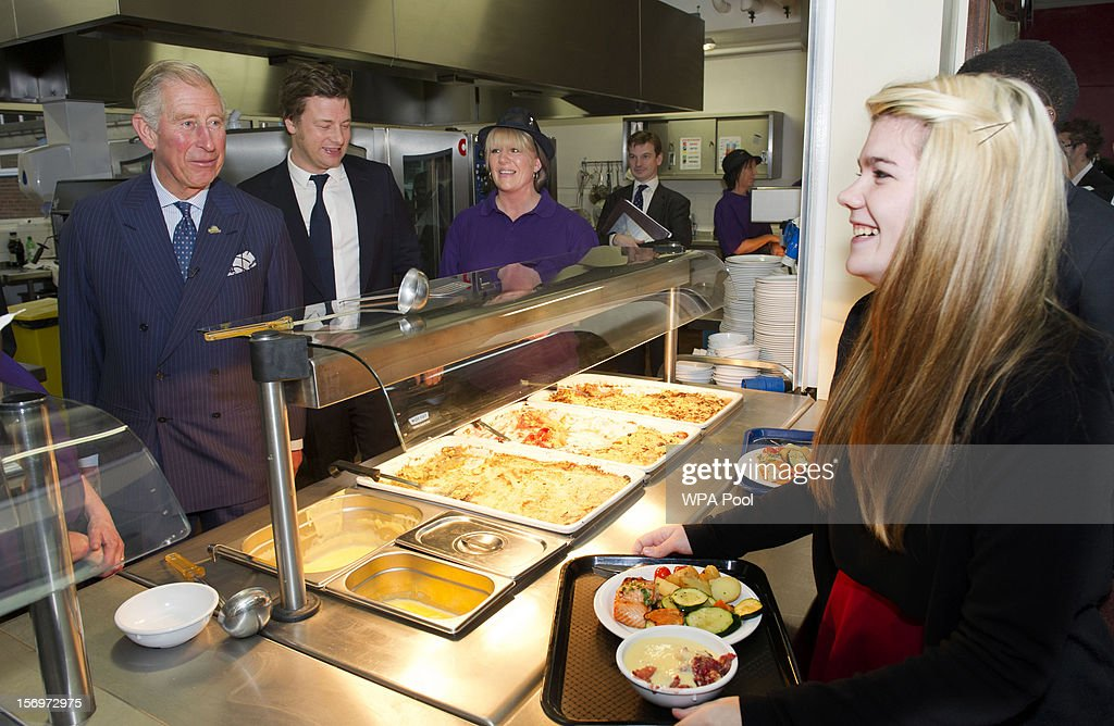 Prince Charles, Prince of Wales shares a joke with Rosir Wastell, 17, after serving rhubarb crumble during a visit to Carshalton Boys Sports College with Jamie Oliver to see how the school has transformed its approach to healthy eating on November 26, 2012 in Carshalton, England.