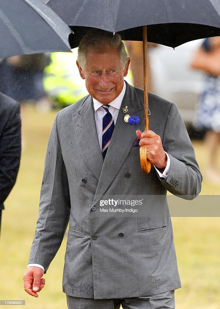 Prince Charles, Prince of Wales shelters under an umbrella as he and Camilla, Duchess of Cornwall visit the 132nd Sandringham Flower Show at Sandringham House on July 31, 2013 in King's Lynn, England.