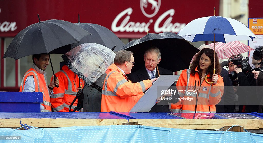 Prince Charles, Prince of Wales shelters under an umbrella as he views the Crossrail development site before travelling on a Metropolitan line underground train from Farringdon to King's Cross on January 30, 2013 in London, England. The Prince of Wales and The Duchess of Cornwall are marking the 150th anniversary of London Underground to emphasise the importance of engineering and infrastructure development in the UK.