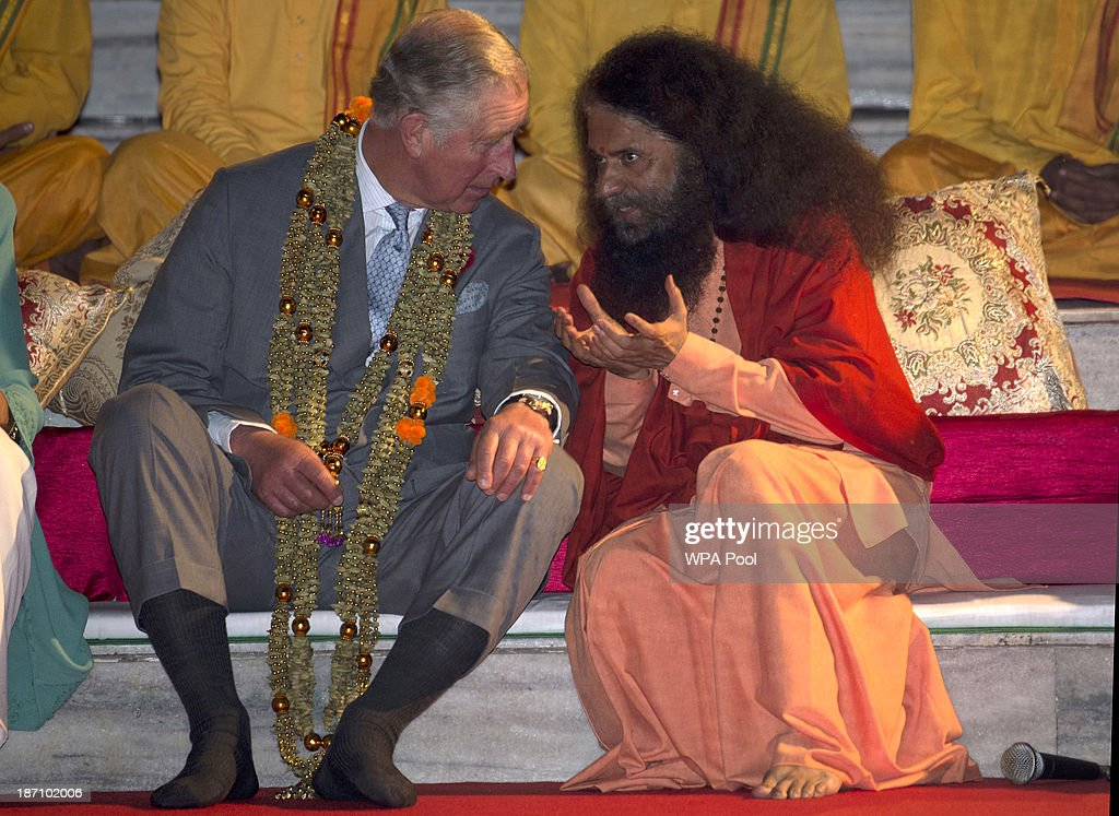 Prince Charles, Prince of Wales takes part in an Aarti ceremony lead by Pujya Swami Chidanand Saraswatiji Maharaj (R) at the Parmarth Niketan Temple on the banks of the River Ganges during day 1 of an official visit to India on November 6, 2013 in Rishikesh, India. This will be the Royal couple's third official visit to India together and their most extensive yet, which will see them spending nine days in India and afterwards visiting Sri Lanka in order to attend the 2013 Commonwealth Heads of Government Meeting.