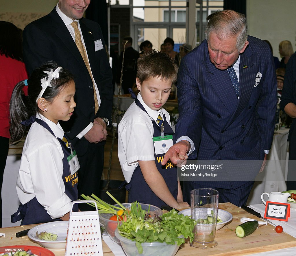 Prince Charles, Prince of Wales talks with school children doing a cookery demonstration as he, accompanied by Jamie Oliver, visits Carshalton Boys Sports College to see how the school has transformed its approach to healthy eating on November 26, 2012 in Carshalton, England.