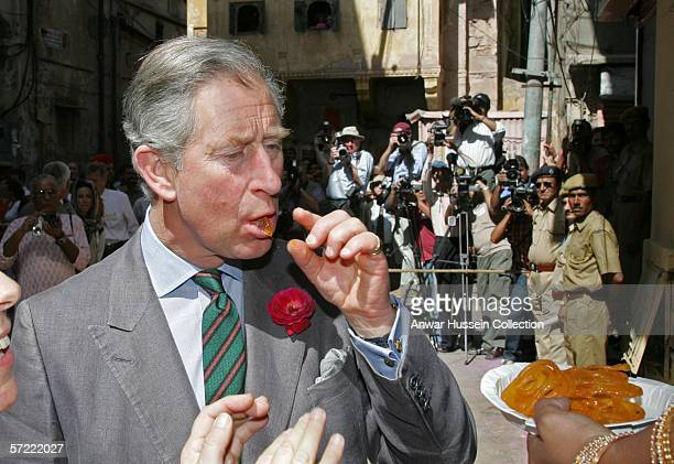 Prince Charles Prince of Wales tastes an Indian sweetmeat as he takes a walking tour of the Old City on the final day of a 12 day official tour...