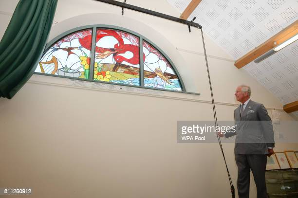 Prince Charles Prince of Wales unveils a new stained glass window on the theme of Welsh legends created by local people at Myddfai Community Hall in...
