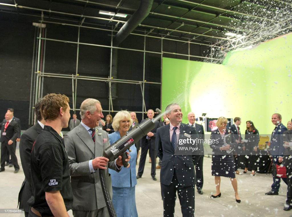 <a gi-track='captionPersonalityLinkClicked' href=/galleries/search?phrase=Prince+Charles&family=editorial&specificpeople=160180 ng-click='$event.stopPropagation()'>Prince Charles</a>, Prince of Wales uses a snow gun as <a gi-track='captionPersonalityLinkClicked' href=/galleries/search?phrase=Camilla+-+Duchess+of+Cornwall&family=editorial&specificpeople=158157 ng-click='$event.stopPropagation()'>Camilla</a>, Duchess of Cornwall looks on as they meet members of the cast and production team during their visit to the set of the BBC One drama series 'Doctor Who' at BBC Roath Lock Studios on July 3, 2013 in Cardiff, Wales.
