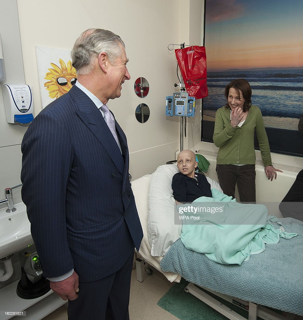 Prince Charles, Prince of Wales visits brain tumor patient Marcus Henson, 11, and mother Julie in the Complimentary therapy massage room at Great Ormond Street Children's hospital on February 21, 2013 in London, England.