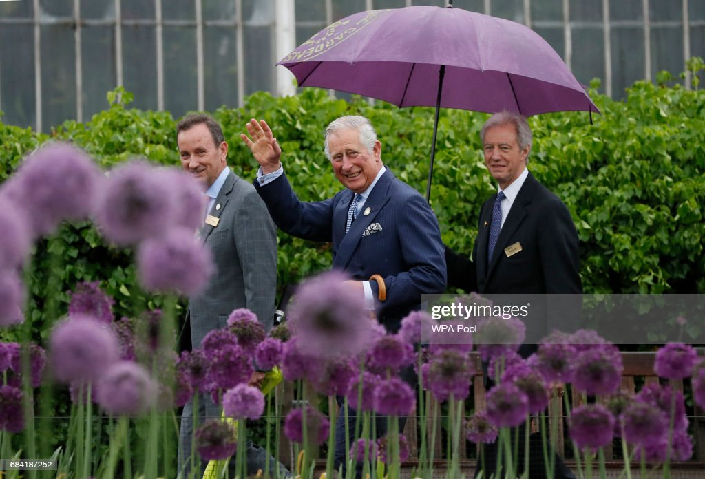 Prince Charles, Prince of Wales waves to the public across a display of alliums during a visit to the Royal Botanic Gardens on May 17, 2017 in London, England. Prince Charles, Prince of Wales attended the launch of the annual State of the World's Plants report and viewed the Great Broad Walk Borders at the Royal Botanic Gardens, Kew.