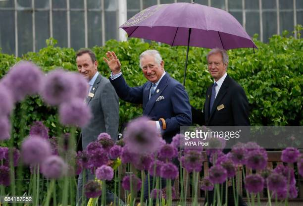 Prince Charles Prince of Wales waves to the public across a display of alliums during a visit to the Royal Botanic Gardens on May 17 2017 in London...