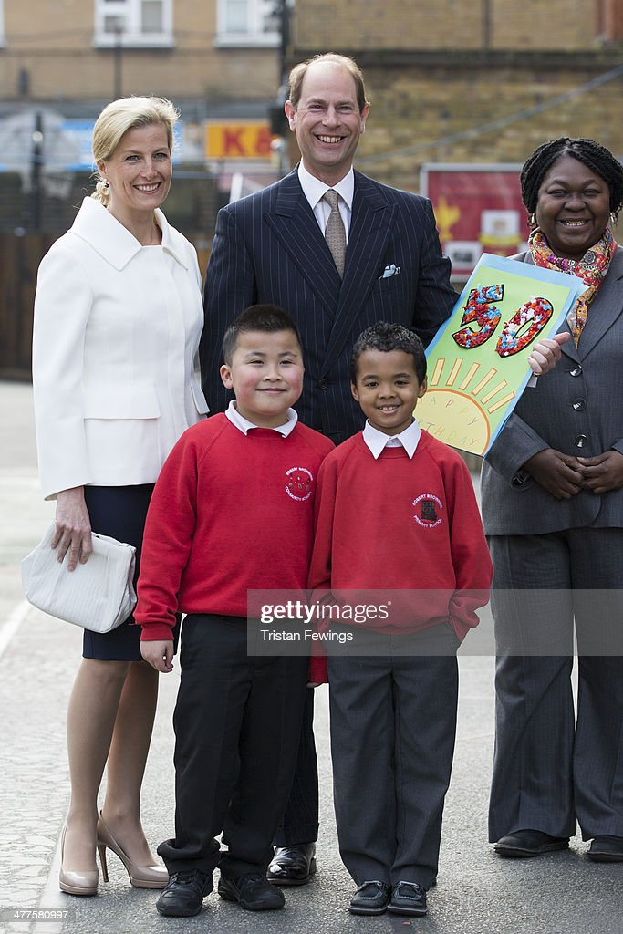 Prince Edward, Earl of Wessex and Sophie, Countess of Wessex pose with pupils and a birthday card during an official visit on the Earl's 50th Birthday at Robert Browning Primary School on March 10, 2014 in London, England.