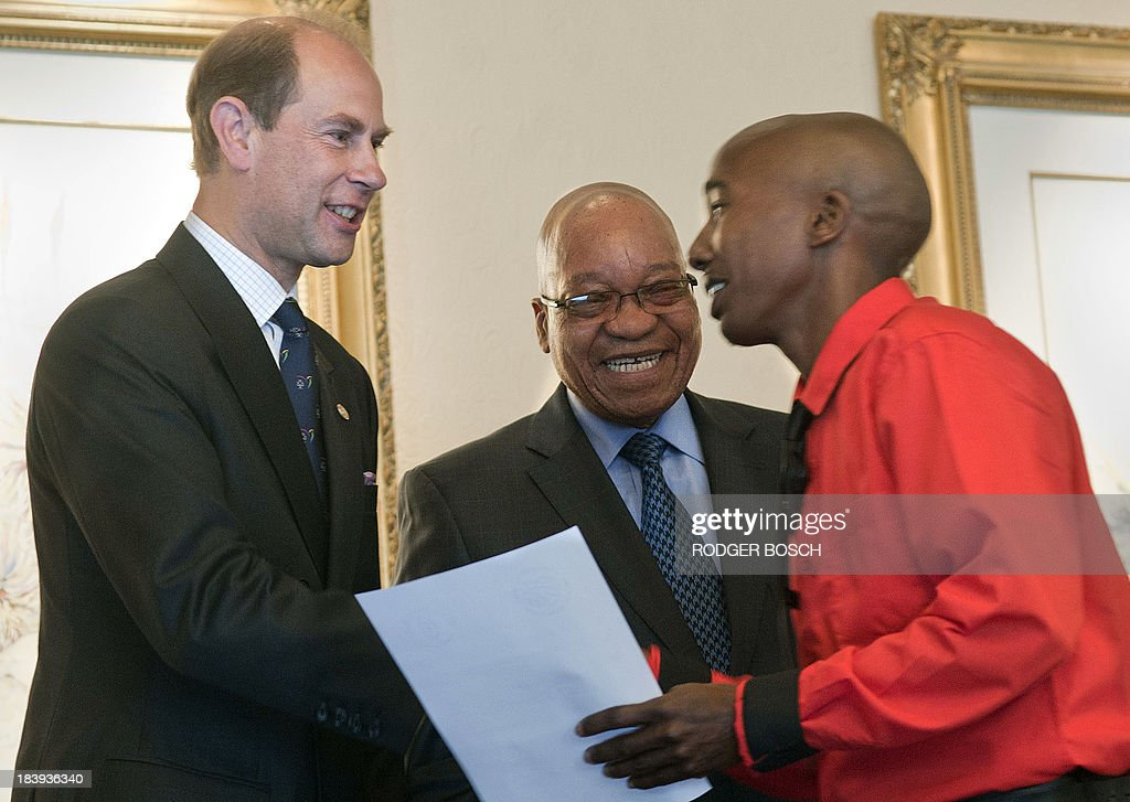Prince Edward, the Earl of Wessex and South African President Jacob Zuma (C) shake hands with one of the recipients of the President's Award for Youth Empowerment on 10 October 2013, at a hotel in Cape Town. The awards are given to young people who have excelled in various fields in conjunction with the Duke of Edinburgh's International Award Foundation. BOSCH