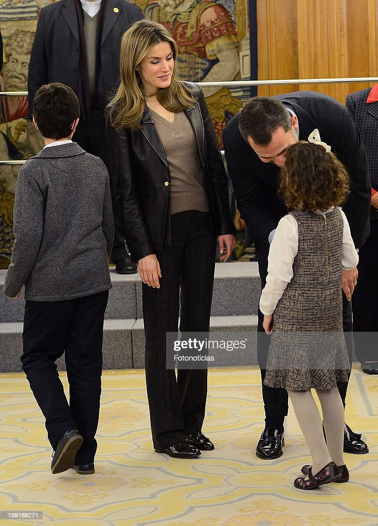 Prince Felipe of Spain (R) and Princess <a gi-track='captionPersonalityLinkClicked' href=/galleries/search?phrase=Letizia+of+Spain&family=editorial&specificpeople=158373 ng-click='$event.stopPropagation()'>Letizia of Spain</a> receive a group of children, winners of a drawing contest, at Zarzuela Palace on January 9, 2013 in Madrid, Spain.