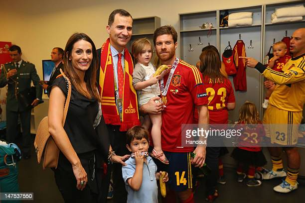 Prince Felipe of Spain poses with Xabi Alonso of Spain and family in the dressing room following the UEFA EURO 2012 final match between Spain and...