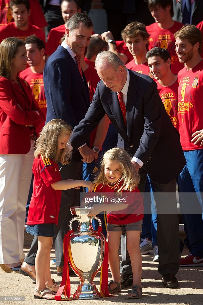 Prince Felipe of Spain smiles as Princess Leonor of Spain and Princess Sofia of Spain play with the UEFA EURO 2012 trophy next to King Juan Carlos I of Spain as they receive the players of the victorious Spain team at Zarzuela Palace on July 2, 2012 in Madrid, Spain.