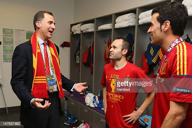 Prince Felipe of Spain speaks to Andres Iniesta and Sergio Busquets of Spain in the dressing room following the UEFA EURO 2012 final match between...