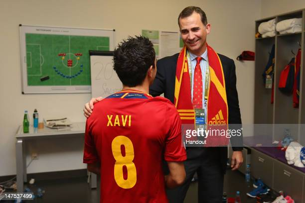 Prince Felipe of Spain speaks to Xavi Hernandez of Spain in the dressing room following the UEFA EURO 2012 final match between Spain and Italy at the...
