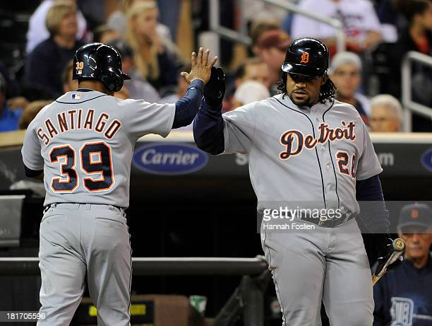 Prince Fielder of the Detroit Tigers congratulates teammate Ramon Santiago on scoring a run against the Minnesota Twins during the fifth inning of...