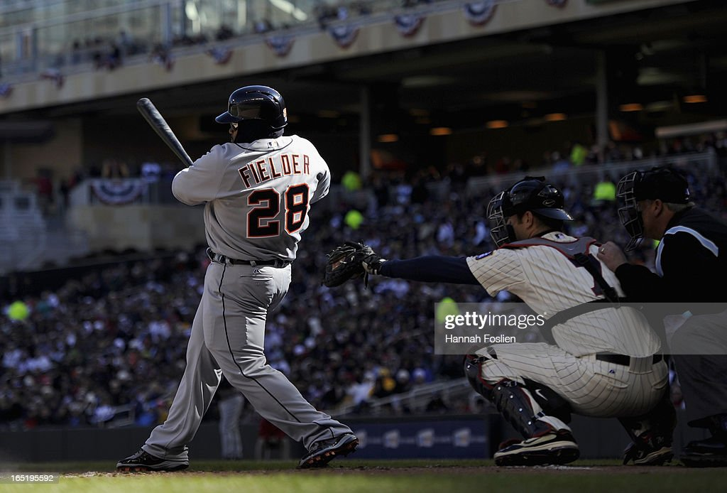 Prince Fielder #28 of the Detroit Tigers hits an RBI double as Joe Mauer #7 of the Minnesota Twins catches during the first inning of the Opening Day game on April 1, 2013 at Target Field in Minneapolis, Minnesota.