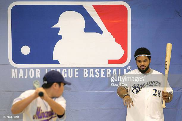 Prince Fielder of the Milwaukee Brewers coaches a member of the baseball club in batting skills while visiting Minamisuna Junior High School as part...