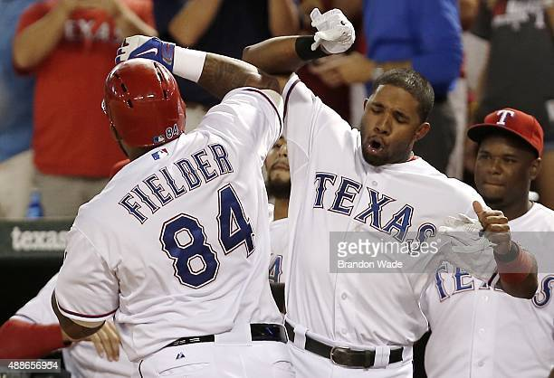 Prince Fielder of the Texas Rangers is congratulated by teammate Elvis Andrus after hitting a solo homerun during the third inning of a baseball game...