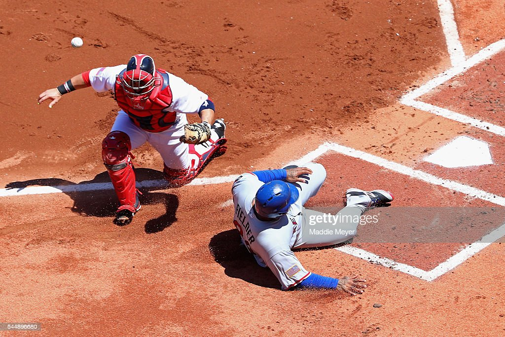 Prince Fielder #84 of the Texas Rangers slides past Sandy Leon #3 of the Boston Red Sox to score during the first inning at Fenway Park on July 4, 2016 in Boston, Massachusetts.