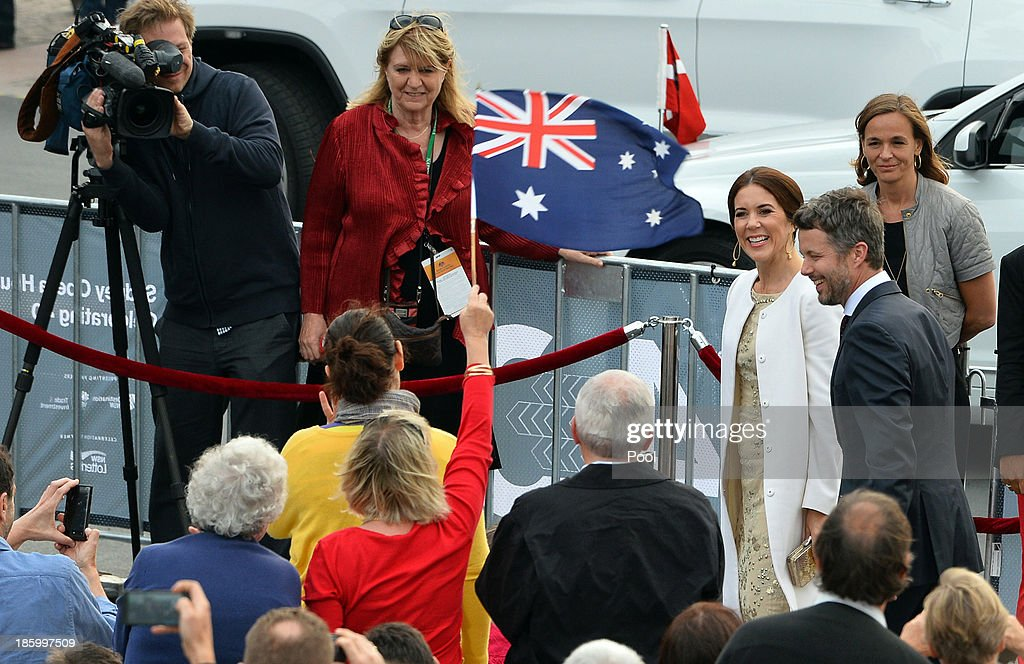 Prince Frederik and Princess Mary of Denmark smile as a women waves flag to greet them ahead of the 40th Anniversary Gala Concert for the Sydney Opera House on October 27, 2013 in Sydney, Australia. Prince Frederik and Princess Mary will visit Sydney for five days and will attend events to celebrate the 40th anniversary of the Sydney Opera House and the Danish architect who designed the landmark, Jorn Utzen.