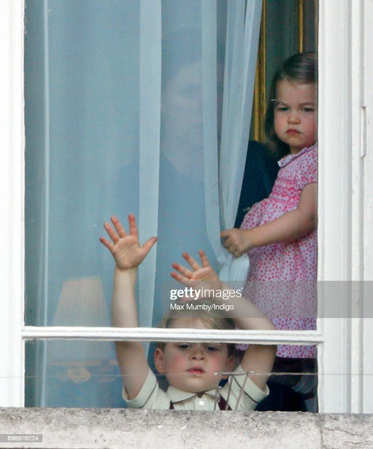 Prince George of Cambridge and Princess Charlotte of Cambridge watch from a window of Buckingham Palace during the annual Trooping the Colour Parade on June 17, 2017 in London, England. Trooping the Colour is a military parade to mark Queen Elizabeth II's official birthday and dates back to the time of Charles II in the 17th Century when the Colours of a Regiment were used as a rallying point in battle.