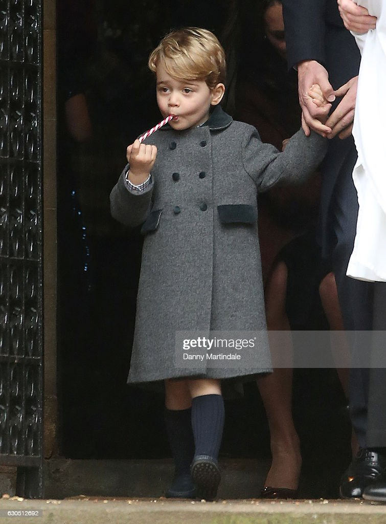 Prince George of Cambridge enjoys a candy cane after attending Church on Christmas Day on December 25, 2016 in St Marks' Church in Englefield, Berkshire.