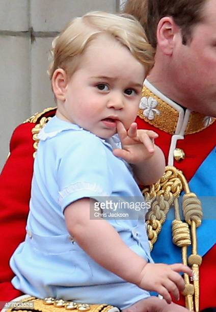 Prince George of Cambridge is held by Prince William Duke of Cambridge as they look out from the balcony of Buckingham Palace during the Trooping the...