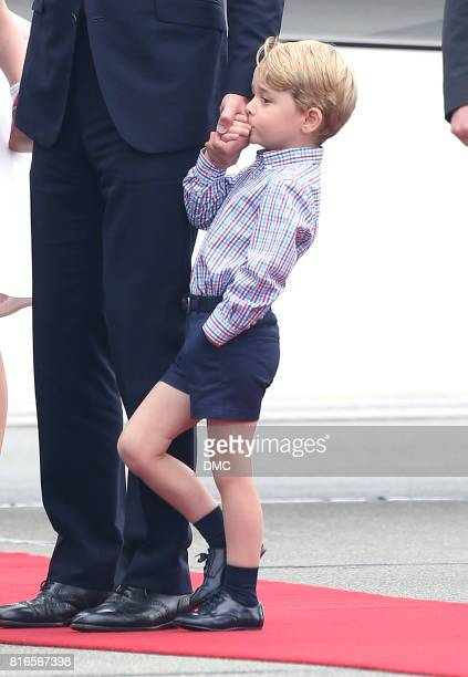 Prince George of Cambridge kisses his father Prince William Duke of Cambridge hand as they arrive at Warsaw Airport during an official visit to...