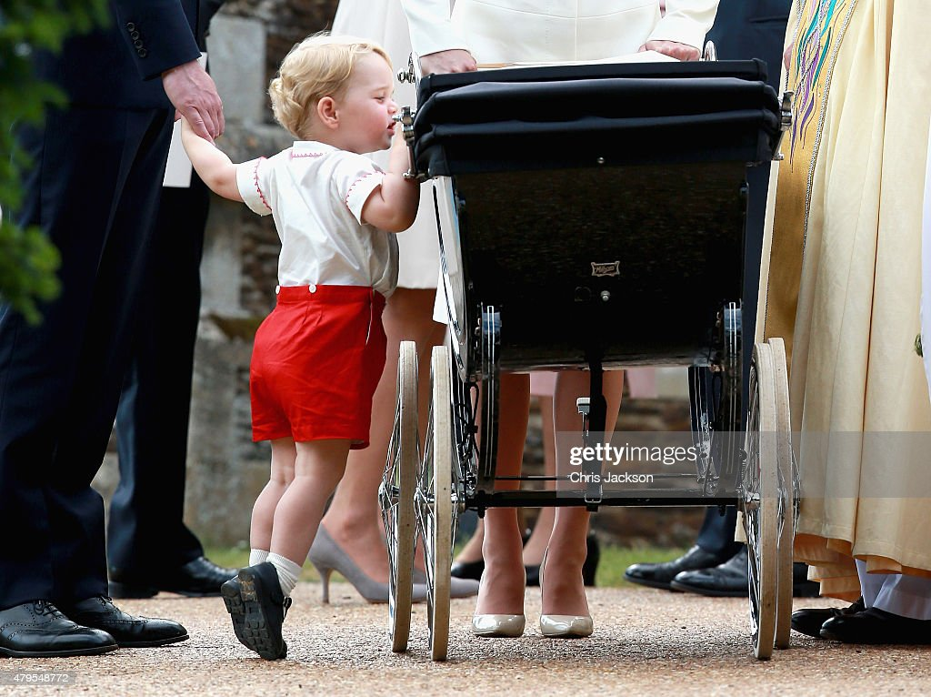 Prince George of Cambridge looks at his sister Princess Charlotte of Cambridge in her pram as he leaves the Church of St Mary Magdalene on the Sandringham Estate for the Christening of Princess Charlotte of Cambridge on July 5, 2015 in King's Lynn, England.