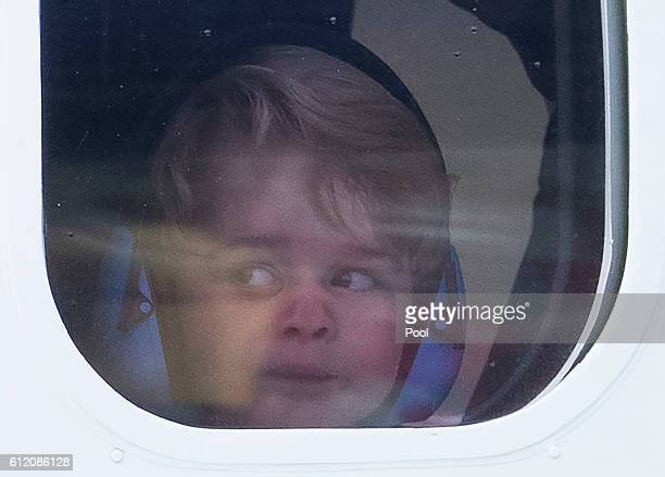 Prince George of Cambridge presses his face against the window as he leaves from Victoria Harbour aboard a seaplane on the final day of their Royal...