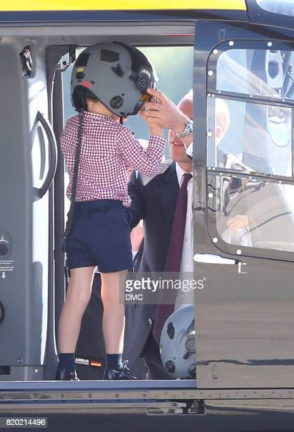 Prince George of Cambridge puts on a helmet with a little help from his father Prince William Duke of Cambridge during a visit to the Airbus factory...