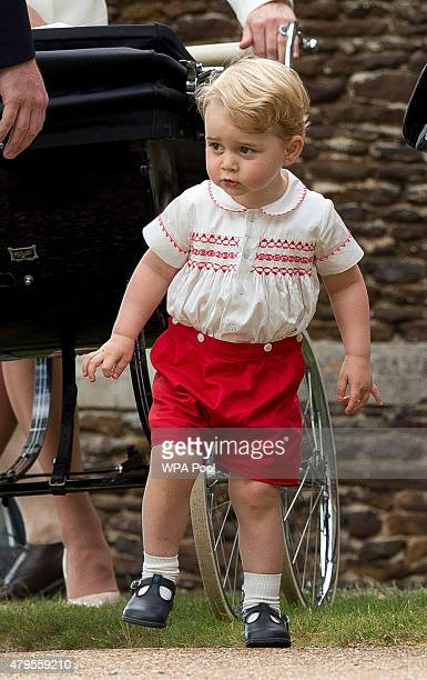 Prince George of Cambridge stands near Princess Charlotte of Cambridge's pram at the Church of St Mary Magdalene on the Sandringham Estate after the...