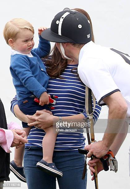Prince George of Cambridge touches his fathers polo helmet as his mother Catherine Duchess of Cambridge holds him at the Gigaset Charity Polo Match...