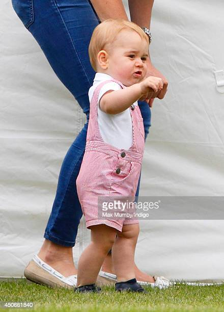 Prince George of Cambridge walks alongside his mother Catherine Duchess of Cambridge as they watch Prince William Duke of Cambridge Prince Harry play...
