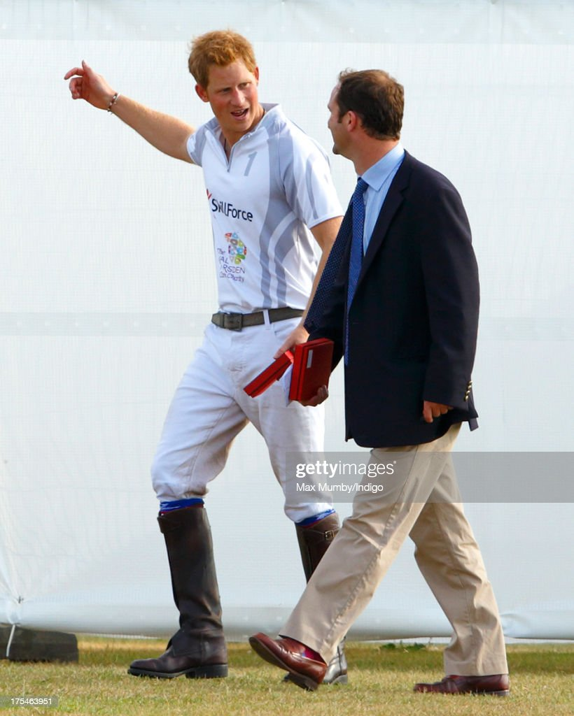 Prince Harry accompanied by Andrew Tucker (Prince William, Duke of Cambridge's & Prince Harry's Polo Manager) attend the prize giving after playing in the Audi Polo Challenge at Coworth Park Polo Club on August 3, 2013 in Ascot, England.