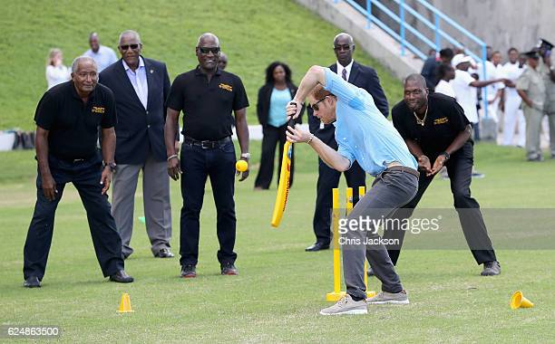 Prince Harry and cricketers Andy Roberts Vivian Richards and Curtly Ambrose attend a youth sports festival at Sir Vivian Richards Stadium showcasing...