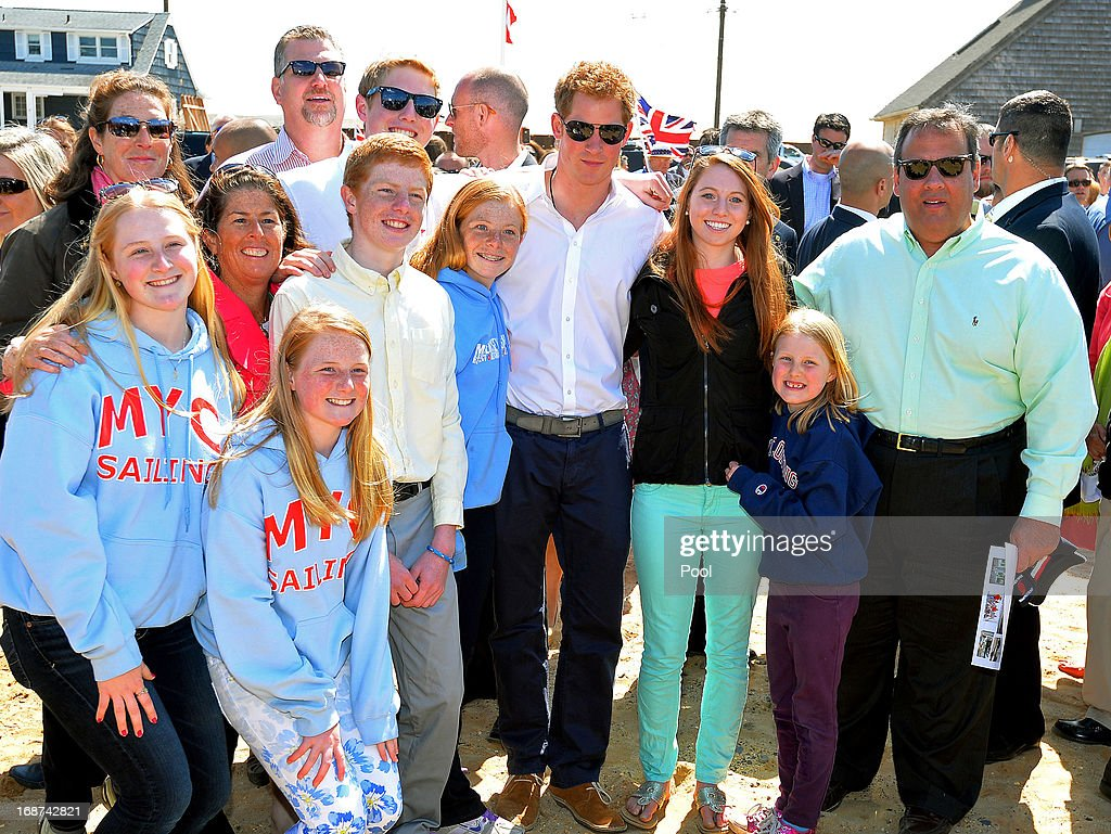 HRH <a gi-track='captionPersonalityLinkClicked' href=/galleries/search?phrase=Prince+Harry&family=editorial&specificpeople=178173 ng-click='$event.stopPropagation()'>Prince Harry</a> and Governor of New Jersey <a gi-track='captionPersonalityLinkClicked' href=/galleries/search?phrase=Chris+Christie&family=editorial&specificpeople=6480114 ng-click='$event.stopPropagation()'>Chris Christie</a> pose for a photograph with a family during his visit to Mantoloking, one of the areas affected by Superstorm Sandy on the fifth day of his visit to the United States on May 14, 2013 in Ocean Heights, New Jersey. HRH will be undertaking engagements on behalf of charities with which the Prince is closely associated on behalf also of HM Government, with a central theme of supporting injured service personnel from the UK and US forces.