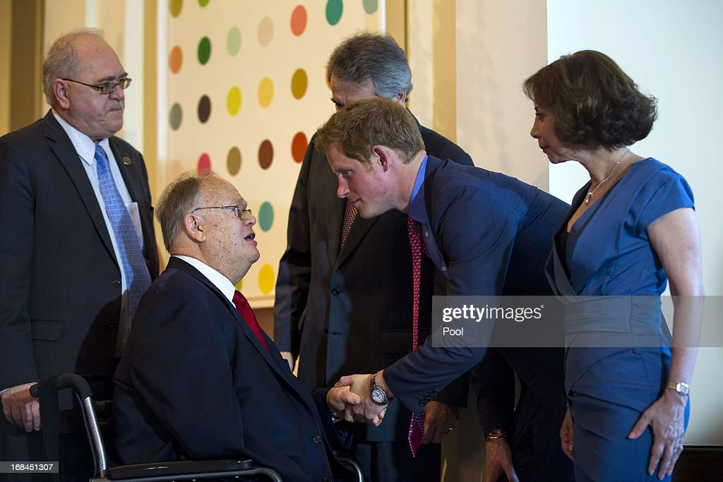 Prince Harry (C) and Lady Westmacott (R) greet former Democratic Senator from Georgia Max Cleland (L) at a dinner at the British Ambassador's residence on May 9, 2013 in Washington, DC.