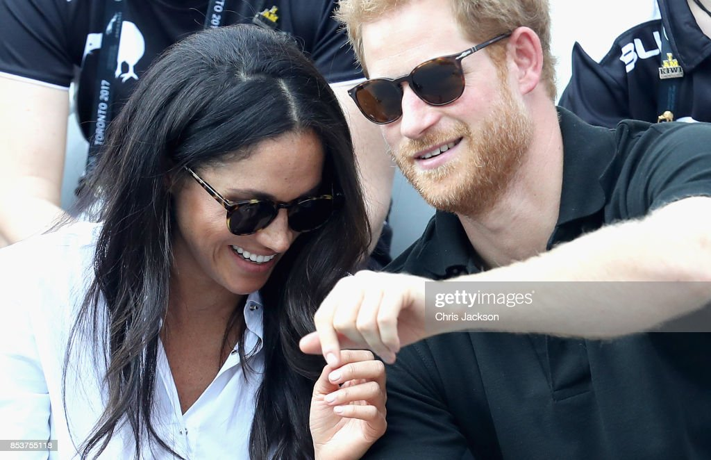 Prince Harry (R) and Meghan Markle (L) hold hands a Wheelchair Tennis match during the Invictus Games 2017 at Nathan Philips Square on September 25, 2017 in Toronto, Canada