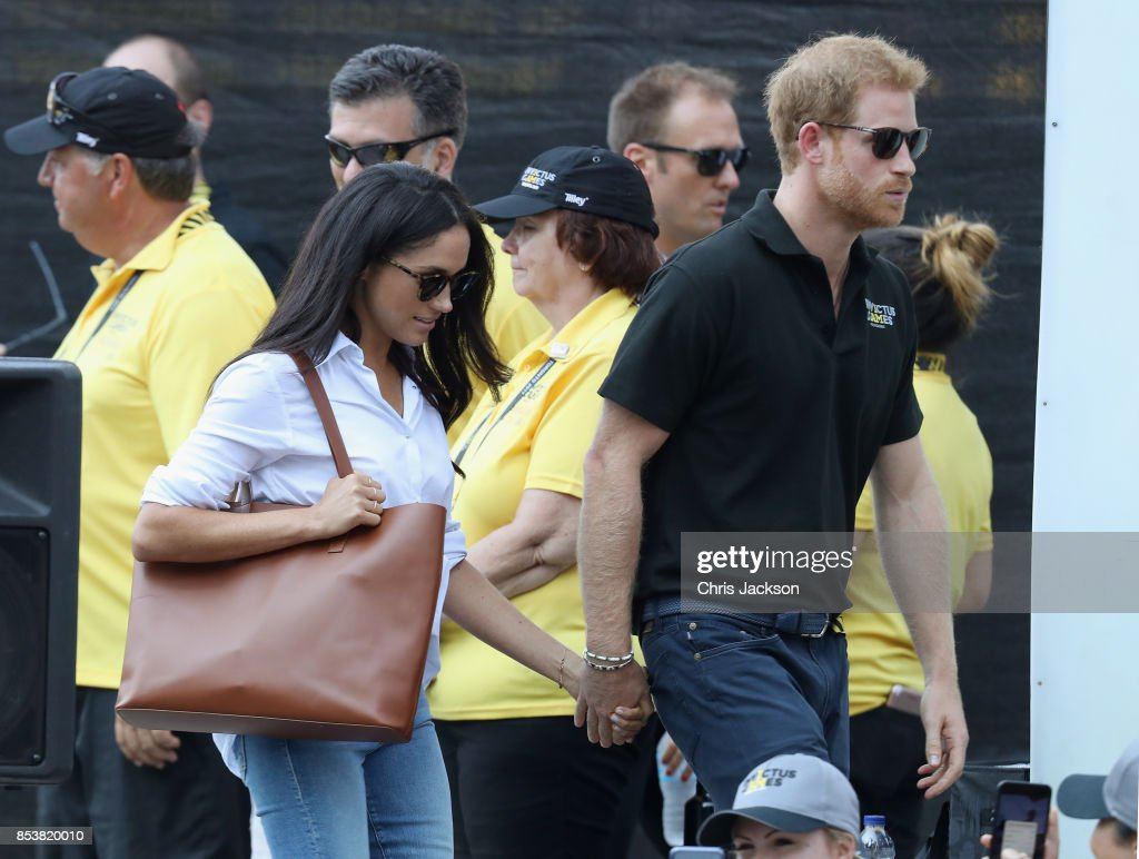 Prince Harry and Meghan Markle hold hands a Wheelchair Tennis match during the Invictus Games 2017 at Nathan Philips Square on September 25, 2017 in Toronto, Canada