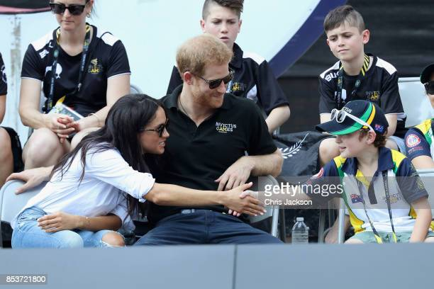Prince Harry and Meghan Markle talk with a child while attending a Wheelchair Tennis match during the Invictus Games 2017 at Nathan Philips Square on...