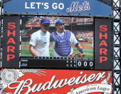 Prince Harry and Mets catcher Rod Barajas displayed on a big screen after Harry pitched the first ball before the New York Mets play the Minnesota...