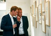 Prince Harry and photographer Chris Jackson view Jackson's photographs based on the work of the Sentebale charity at the private view of the...